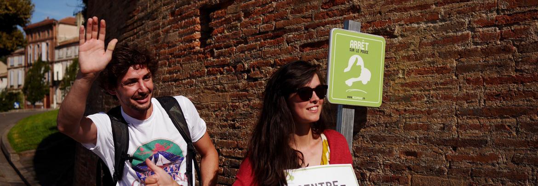 Deux personnes happy attendent à un arrêt sur le pouce